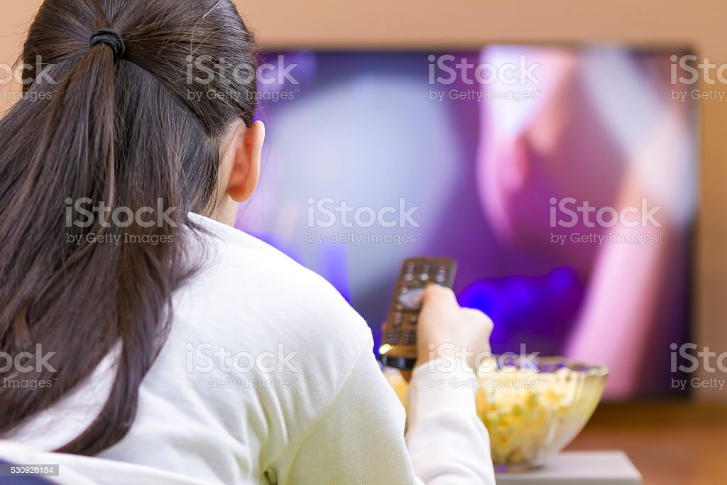 Relaxed teenage girl with remote control watching smart TV stock photo