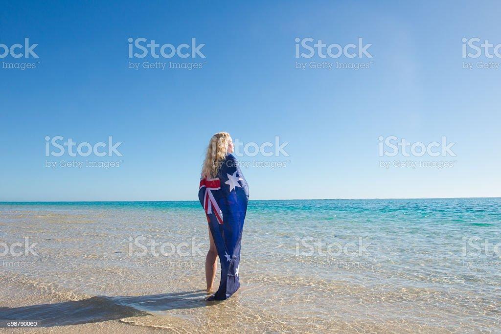Relaxed woman Australian flag at beach stock photo