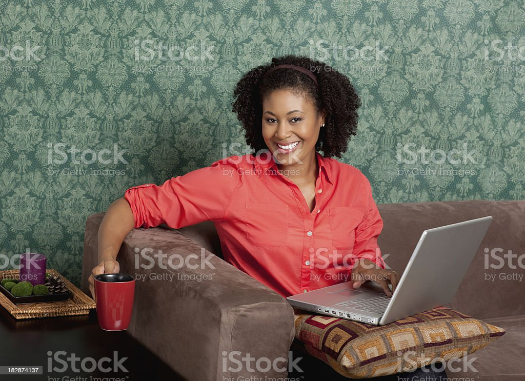 Relaxed woman browsing the internet as she drinks coffee royalty-free stock photo