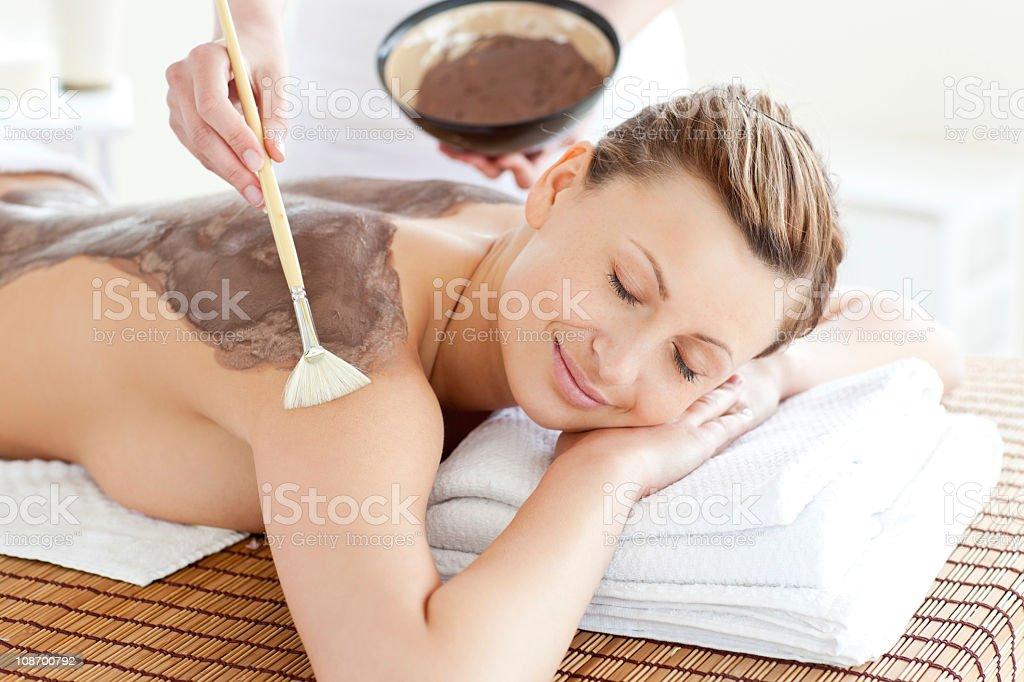 Relaxed woman enjoying a mud skin treatment royalty-free stock photo