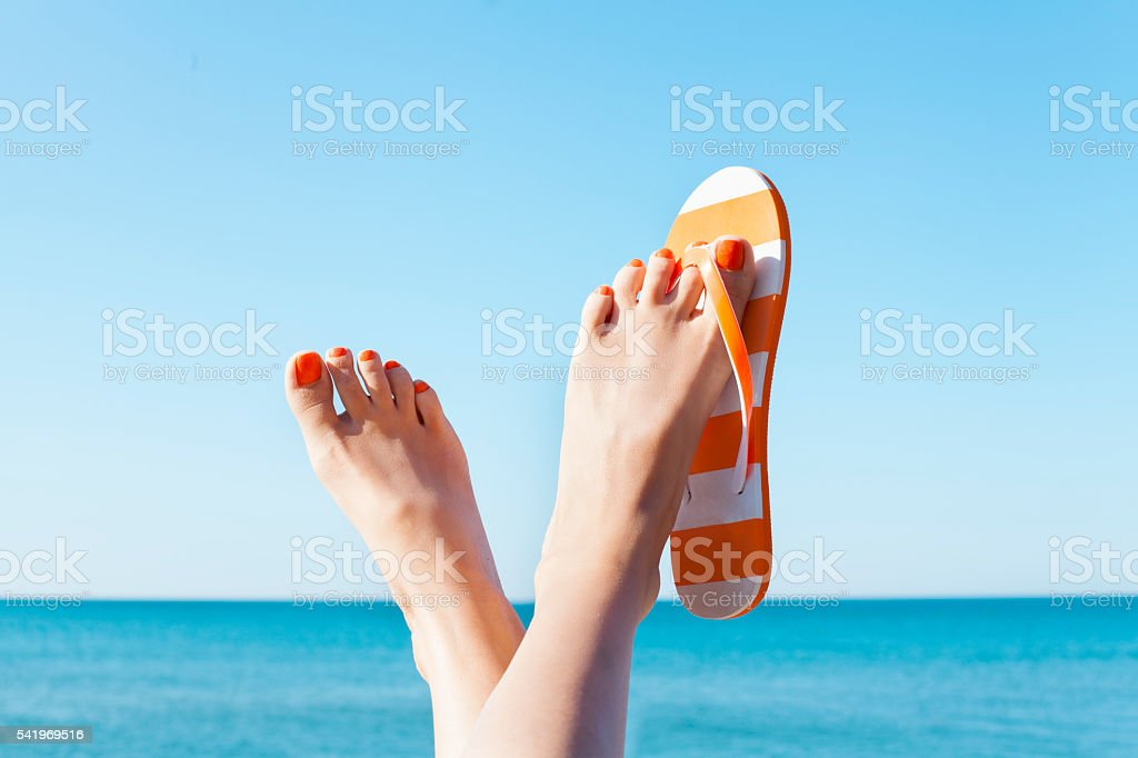 Relaxed woman feet and flip flops on the beach stock photo