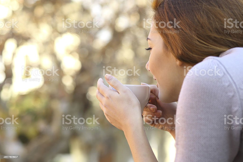Relaxed woman holding a cup of coffee outdoor stock photo