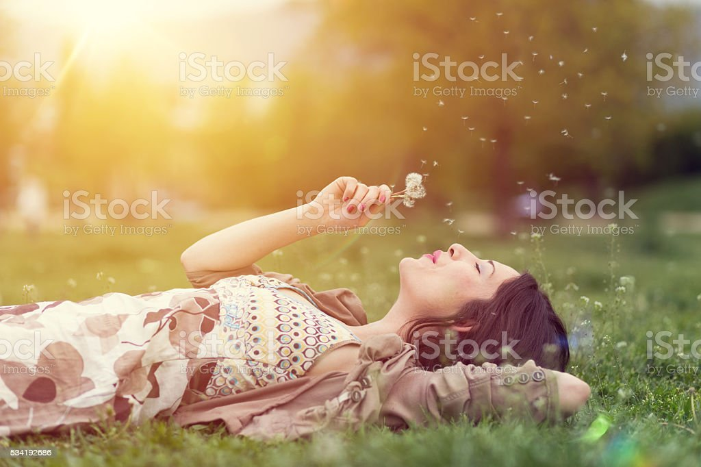 Relaxed woman in the park blowing dandelion stock photo