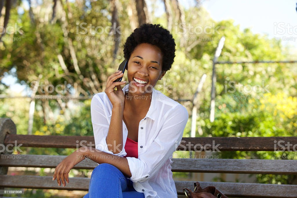 Relaxed woman on a park bench and using cell phone stock photo