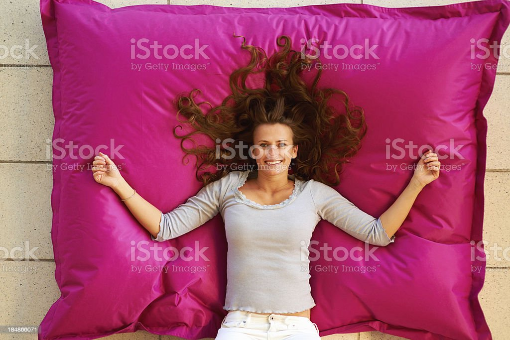 Relaxed woman on pink cushion royalty-free stock photo