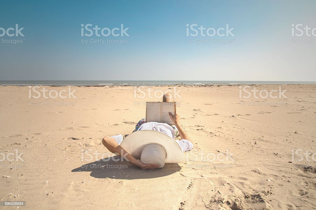 relaxed Woman Reading a book in front of the sea stock photo