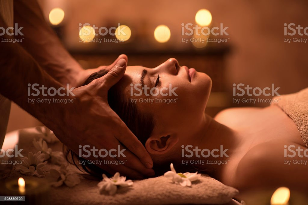 Relaxed woman receiving head massage at spa. stock photo