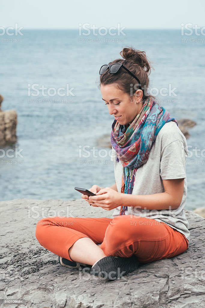 relaxed woman sitting by the sea texting on phone stock photo