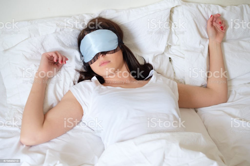 Relaxed woman sleeping in her bed wearing mask stock photo