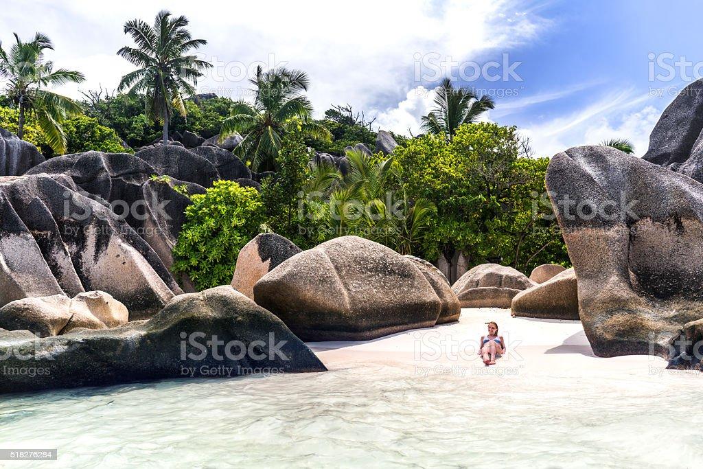 Relaxed woman sunbathing on La Digue island on Seychelles. stock photo
