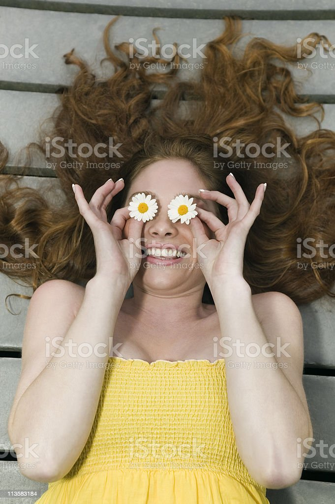 Relaxed woman with flowers over eyes royalty-free stock photo
