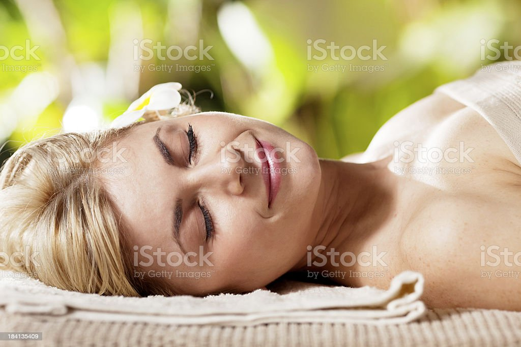 Relaxed young adult woman lying in spa resort royalty-free stock photo