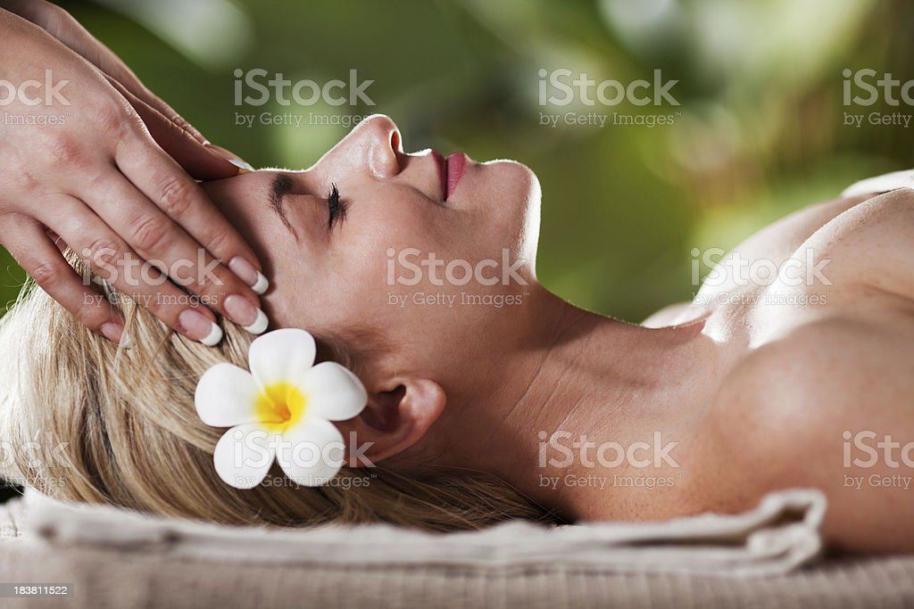 Relaxed young adult woman receiving head massage royalty-free stock photo