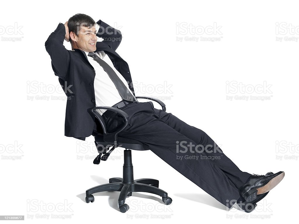 Relaxed young business man sitting in an office chair royalty-free stock photo