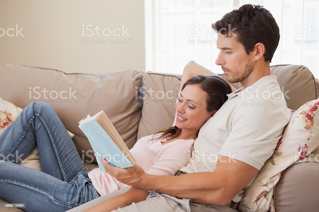 Relaxed young couple reading book on couch stock photo