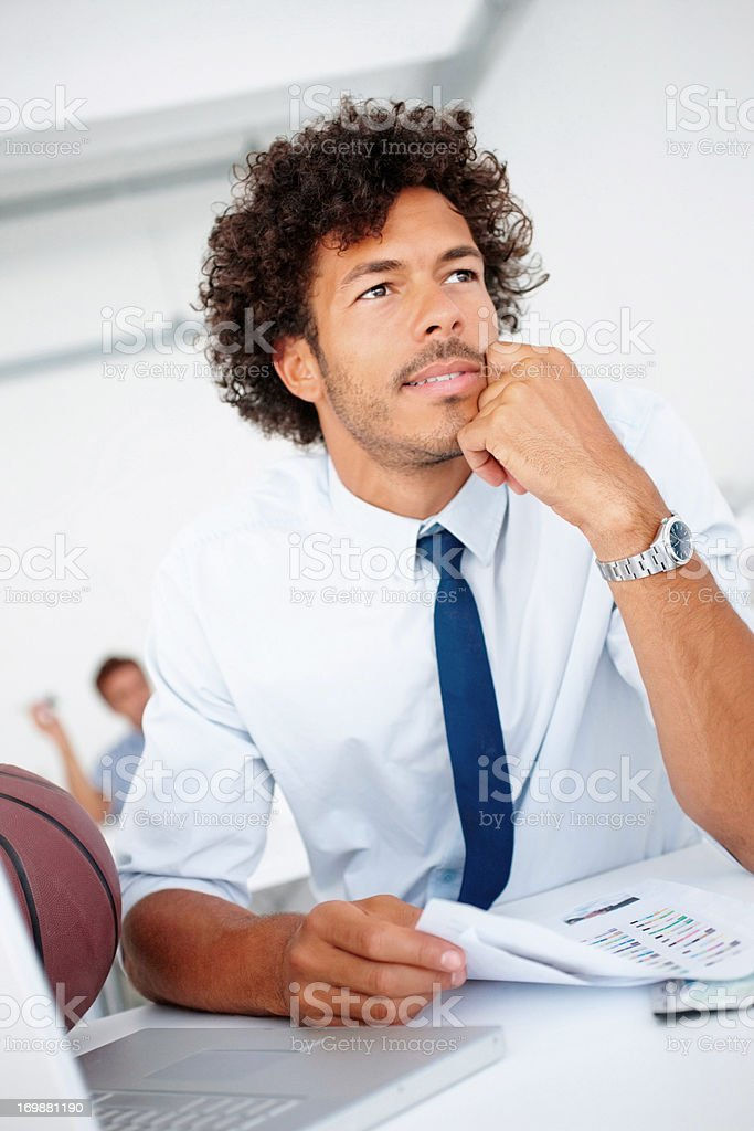 Relaxed young designer at work,seated on his desk stock photo