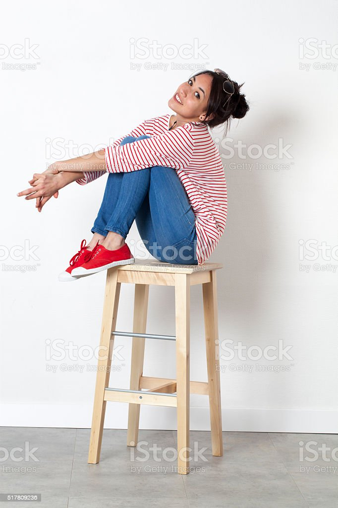 relaxed young ethnic girl sitting on stool with legs crossed stock photo