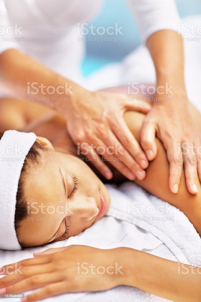 Relaxed young female receiving a shoulder massage royalty-free stock photo