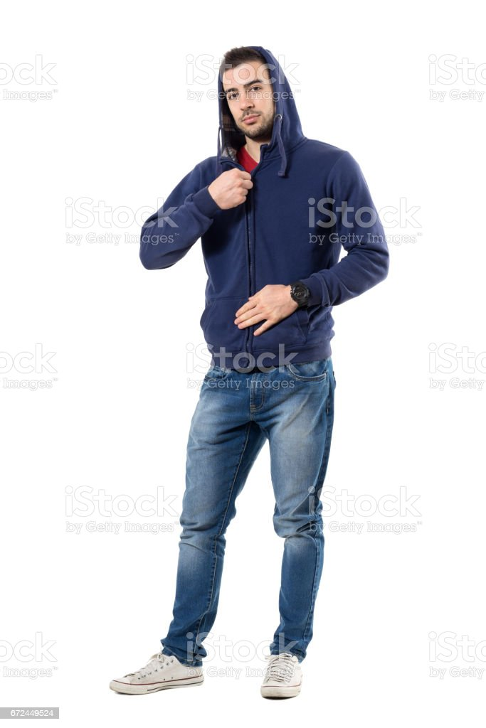 Relaxed young guy fastening zipper on hoodie getting dressed stock photo