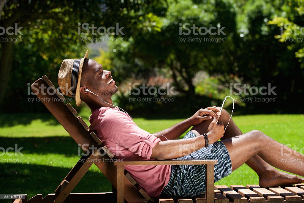 Relaxed young guy listening to music on digital tablet stock photo