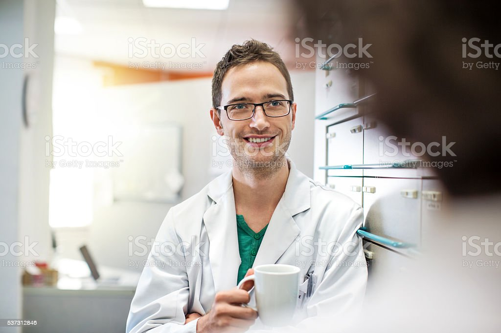 Relaxed young male pharmacists with a cup of coffee stock photo