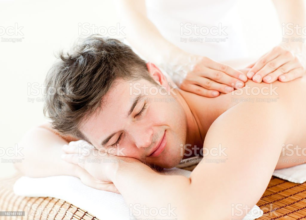 Relaxed young man receiving a back massage royalty-free stock photo