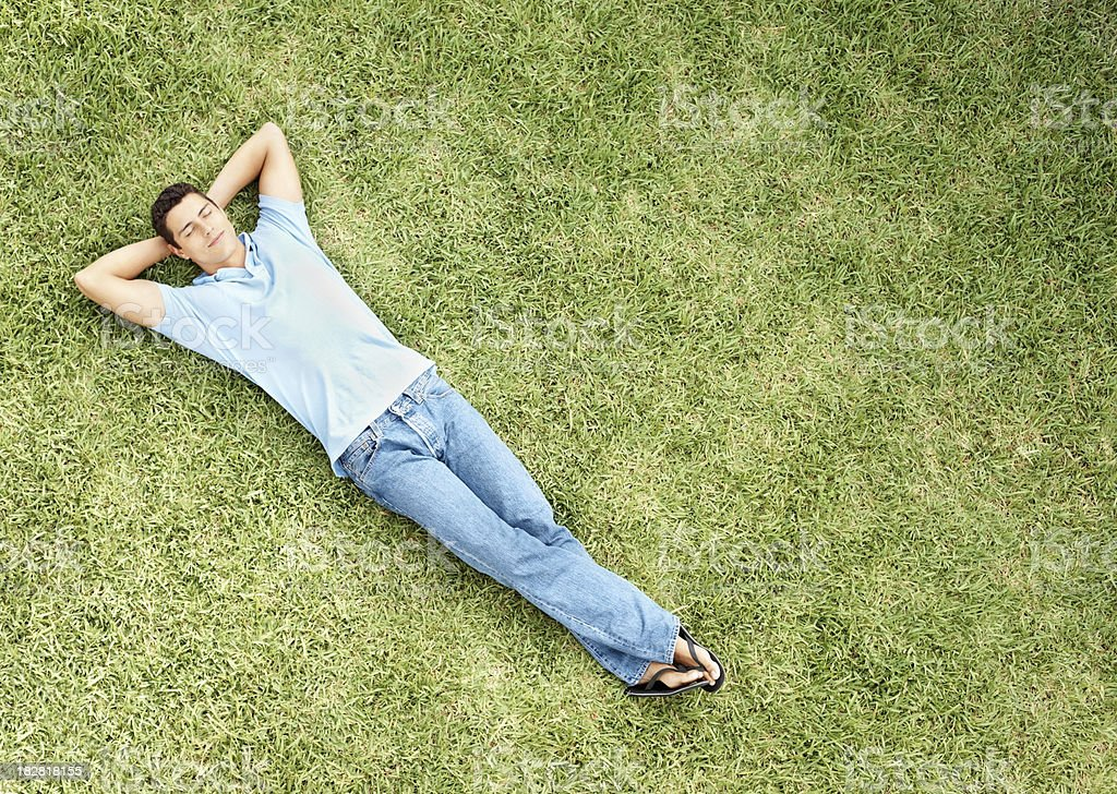 Relaxed young man sleeping on grass stock photo