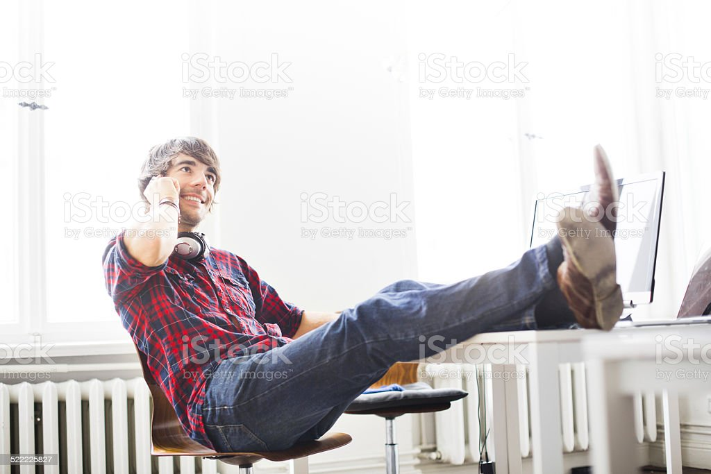Relaxed young man talking on mobile phone stock photo