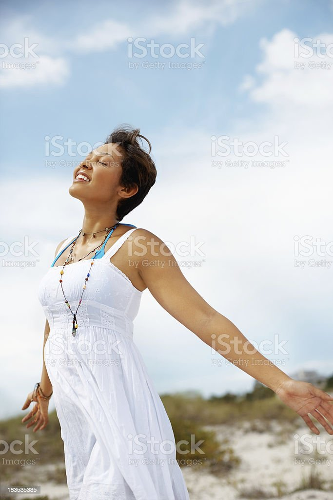 Relaxed, young woman enjoying the fresh air on beach royalty-free stock photo