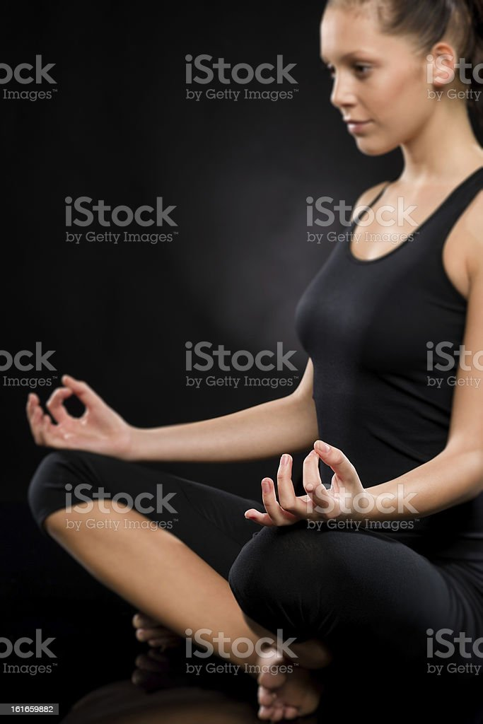 Relaxed young woman exercising in lotus position royalty-free stock photo