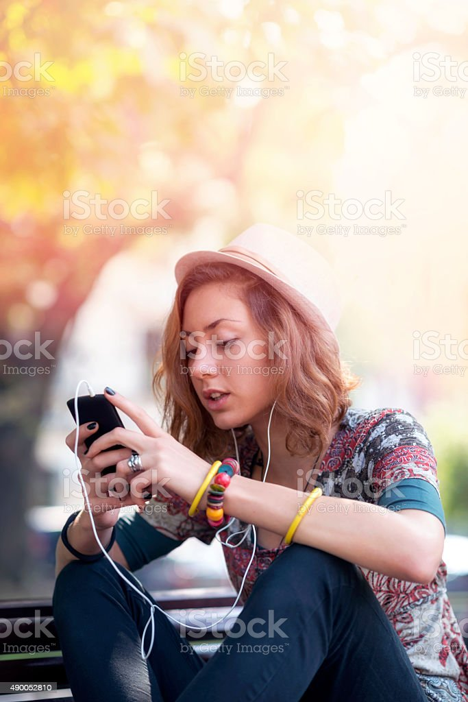 Relaxed young woman listening music in park stock photo