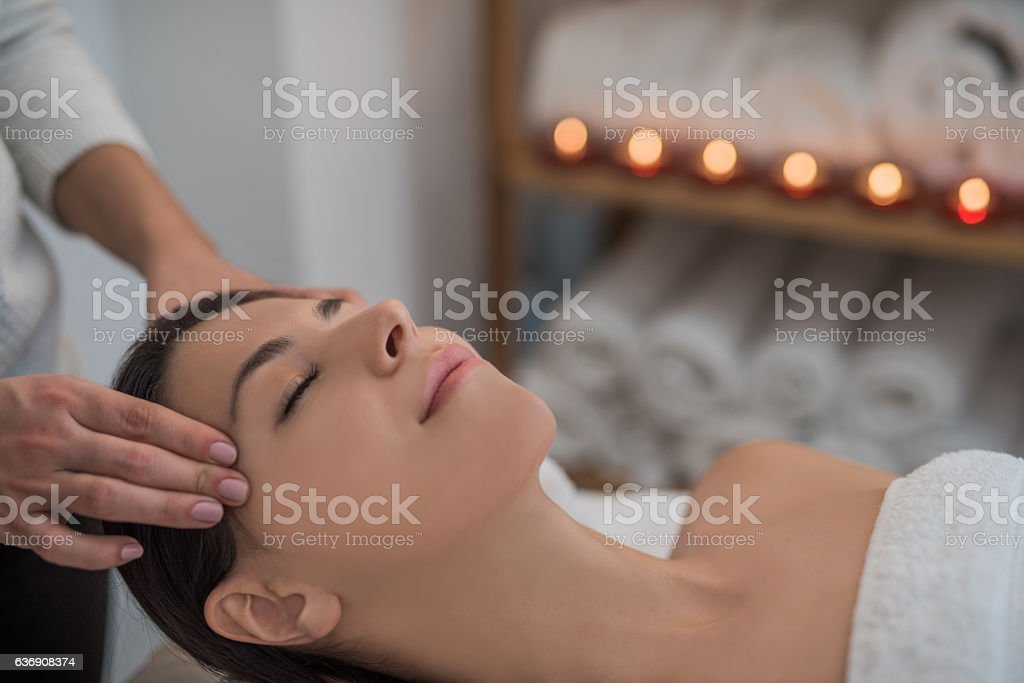 Relaxed young woman receiving an anti-stress temple massage stock photo