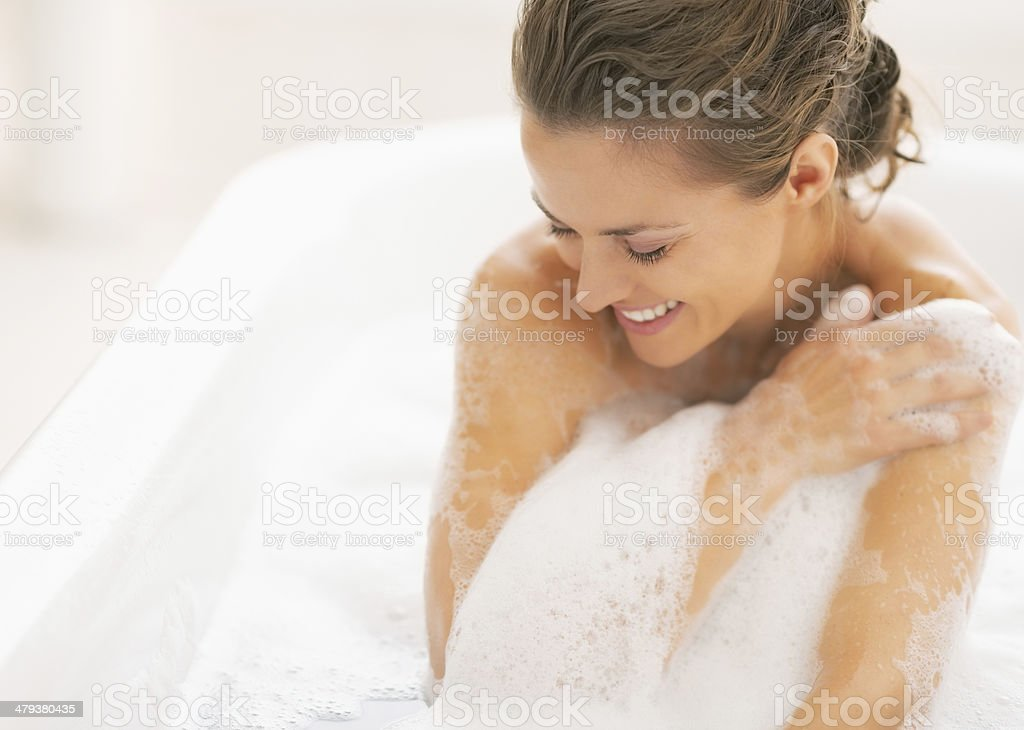 relaxed young woman sitting in bathtub stock photo