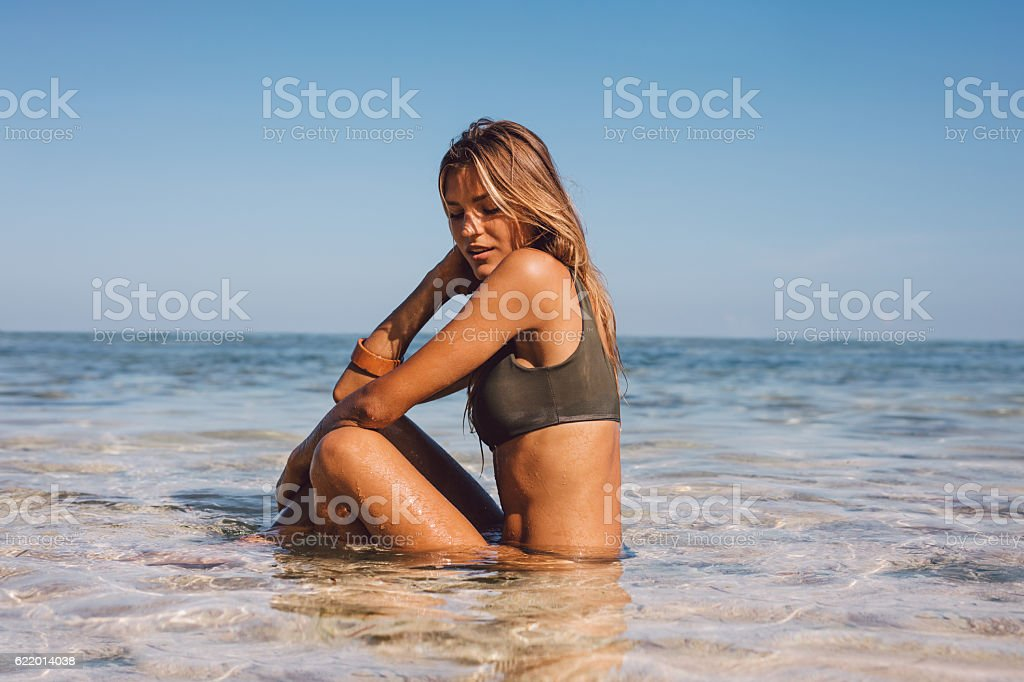 Relaxed young woman sitting in sea water stock photo