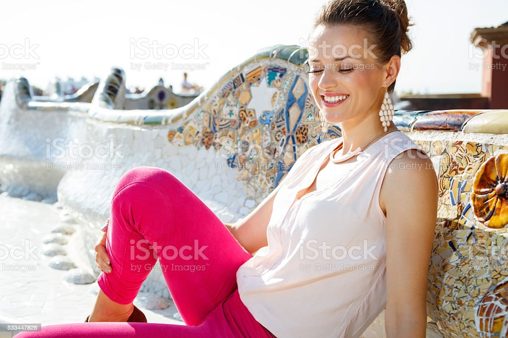 Relaxed young woman sitting on the famous trencadis style bench stock photo