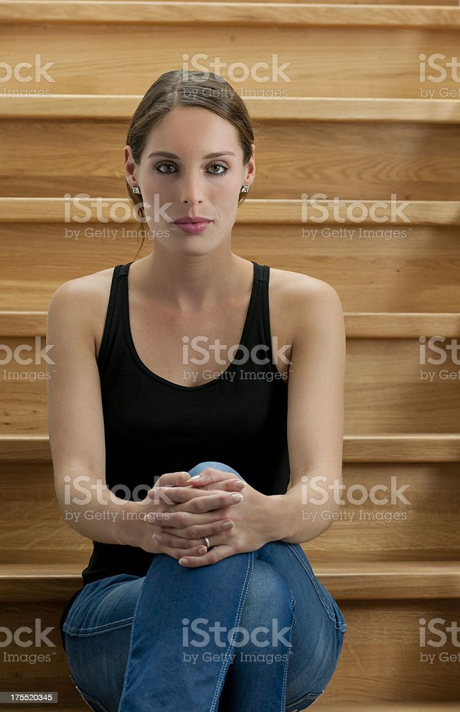 relaxed young woman sitting on wooden staircase royalty-free stock photo
