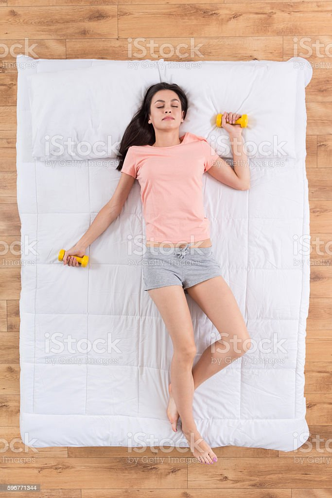 Relaxed young woman sleeping on bed stock photo
