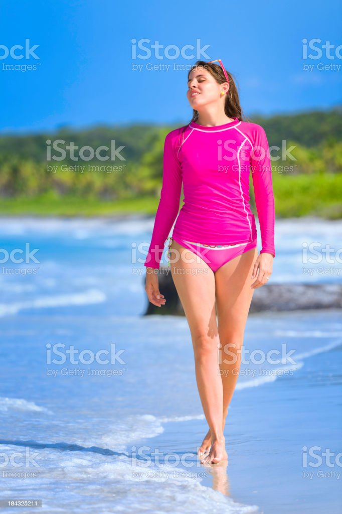 Relaxed young woman walking on a tropical beach royalty-free stock photo