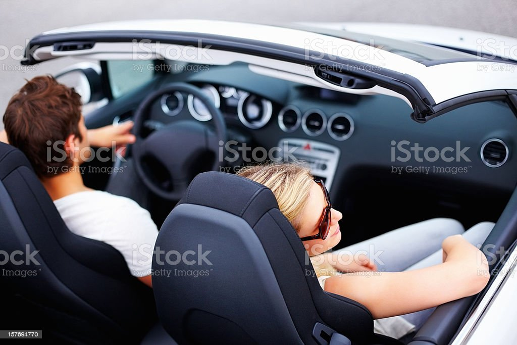 Relaxed, young woman with boyfriend driving a convertible royalty-free stock photo