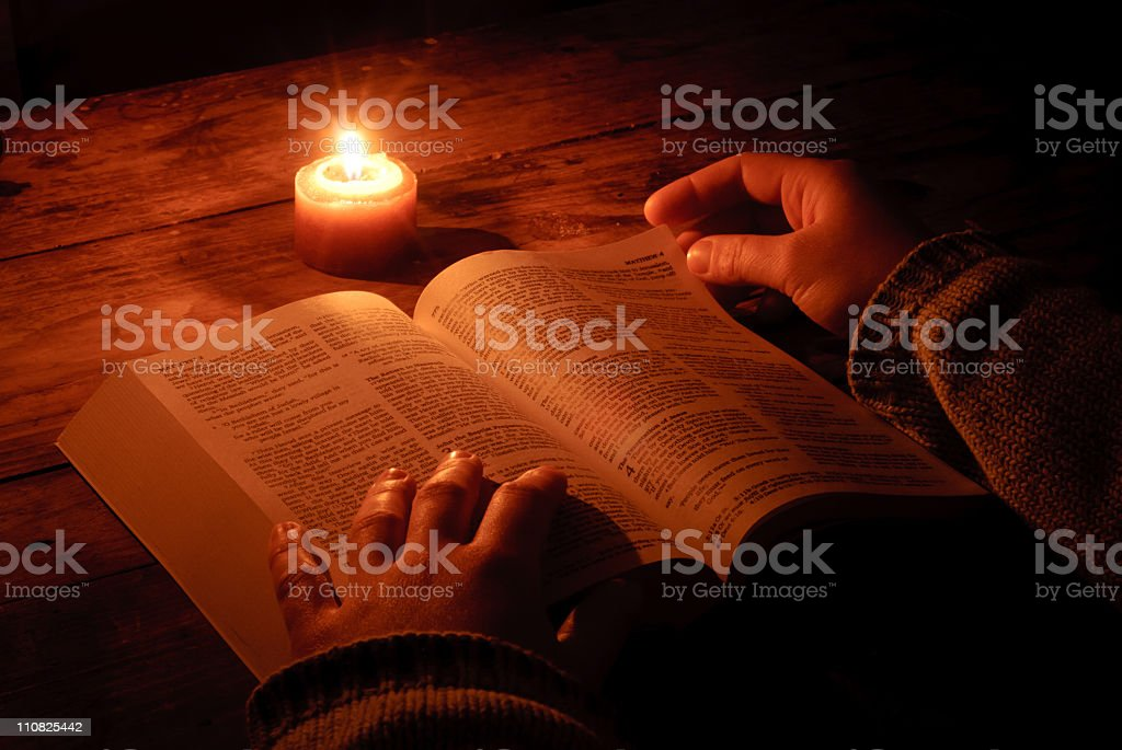 Relaxing and reading bible by candlelight at night stock photo