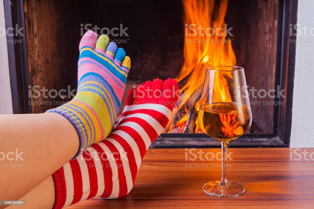 relaxing at fireplace in colorful funny toesocks stock photo