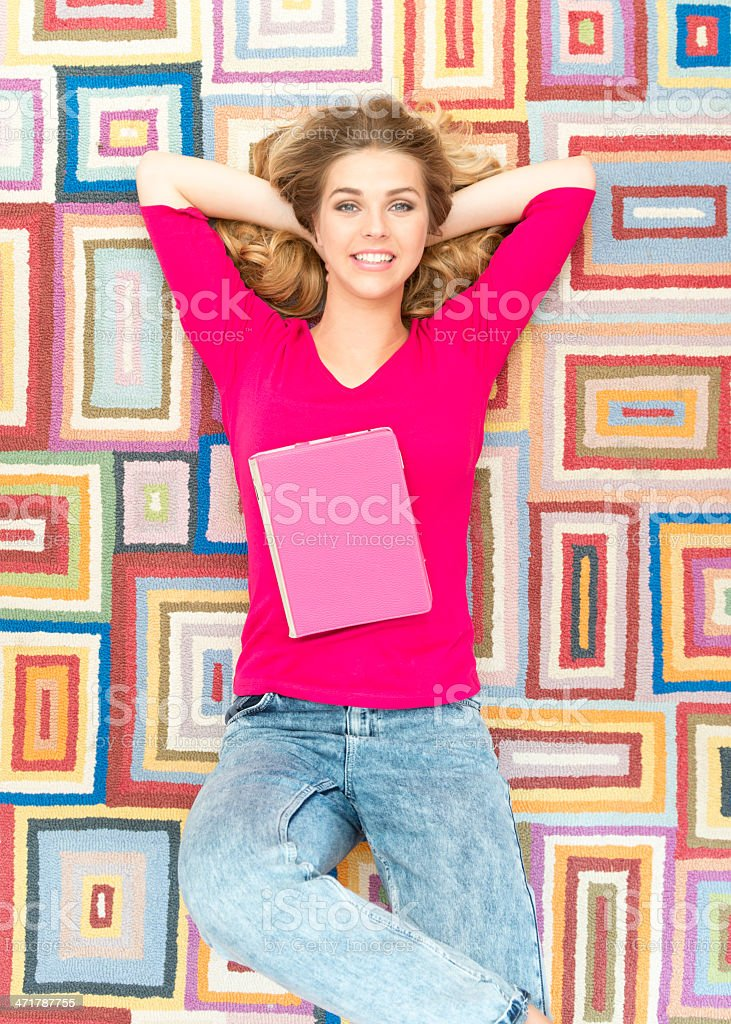 Young woman relaxing at home lying on a brightly coloured patterned...