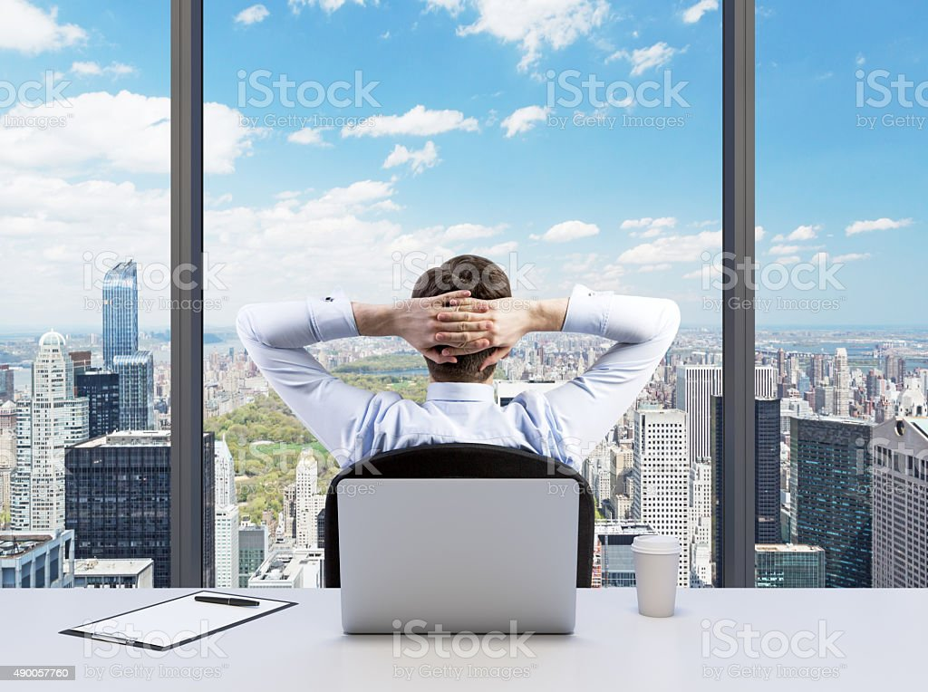 relaxing businessman with crossed hands stock photo