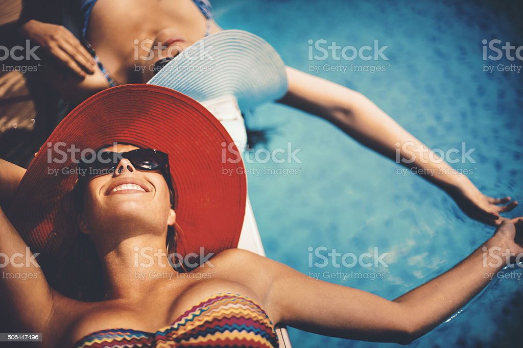 Relaxing by pool side. stock photo