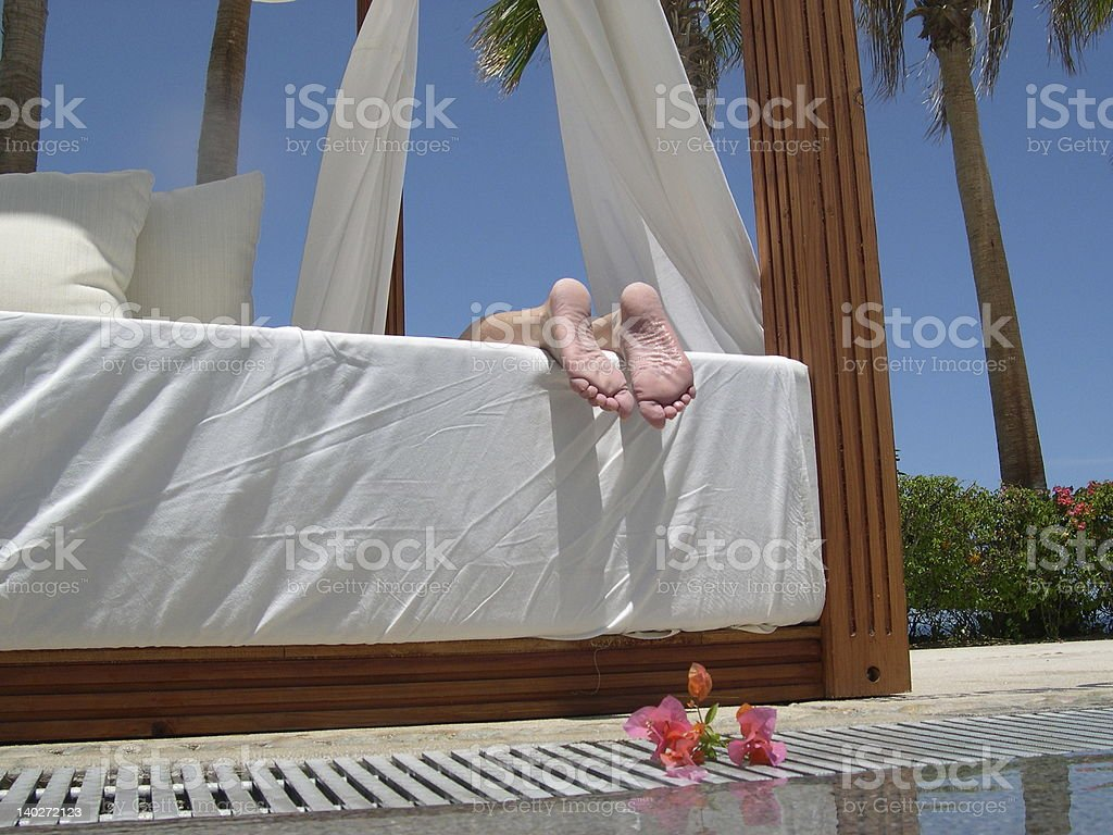 relaxing feet on poolside bed royalty-free stock photo
