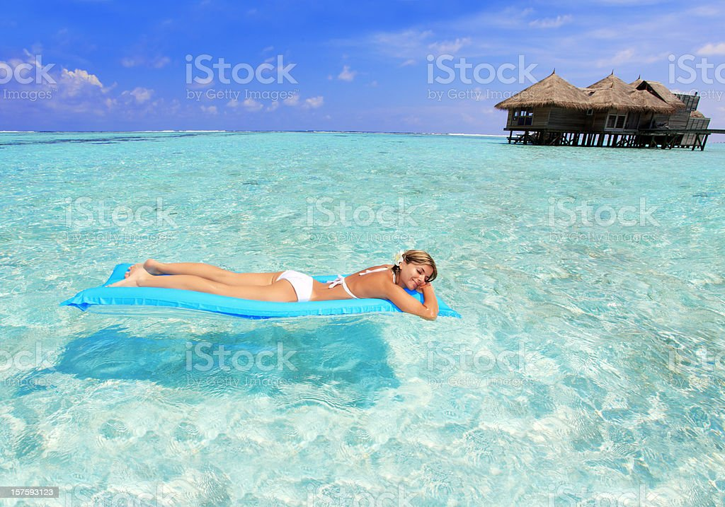 Relaxing girl on inflatable mattress. royalty-free stock photo