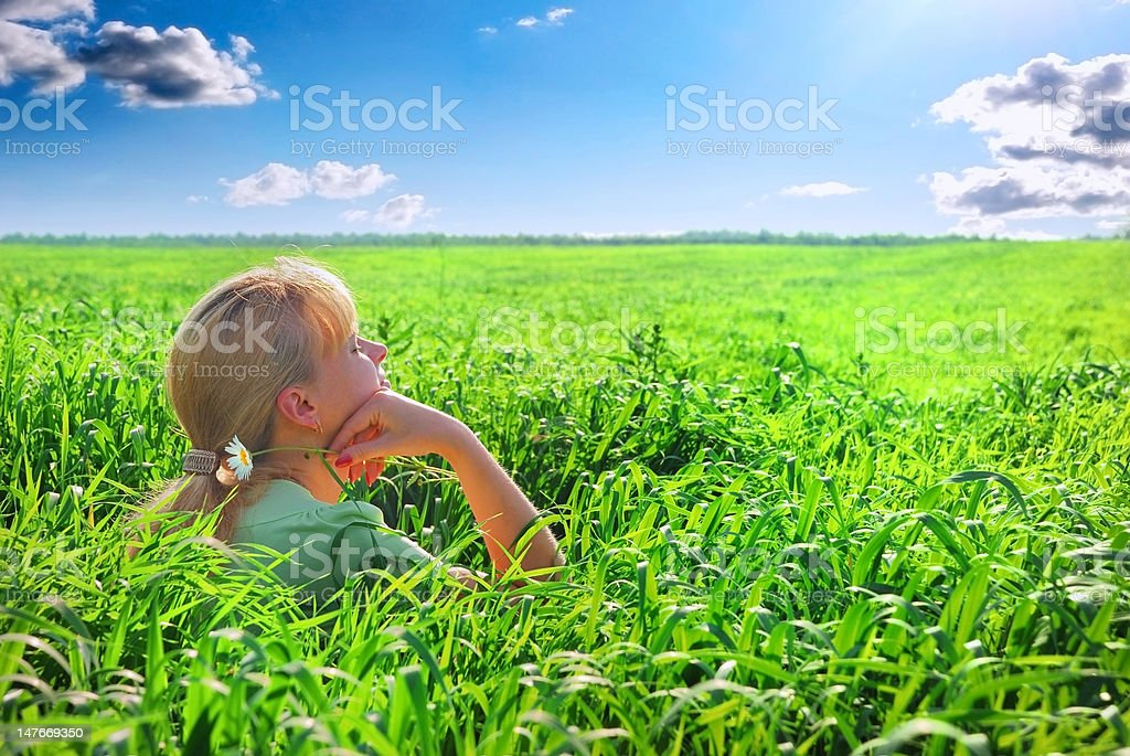 Relaxing girl on meadow against the blue sky royalty-free stock photo