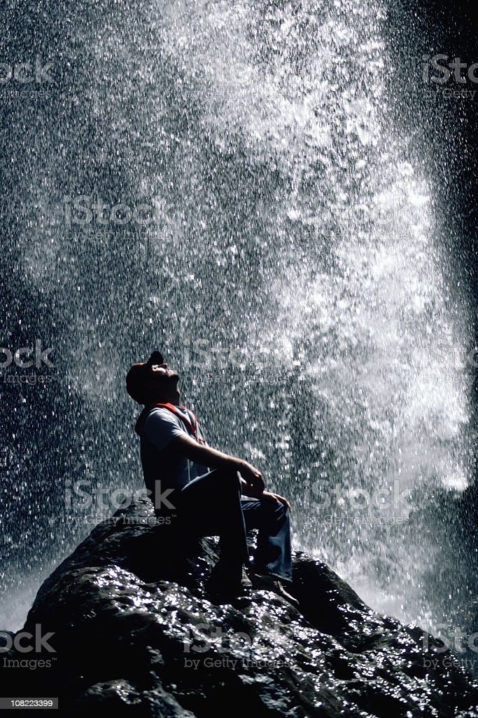 Relaxing Hiker Under Large Cooling Waterfall royalty-free stock photo