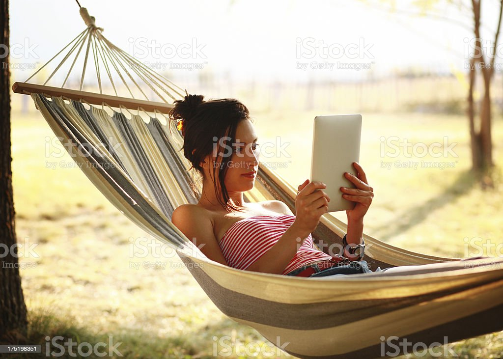 relaxing in hammock with a tablet reader royalty-free stock photo