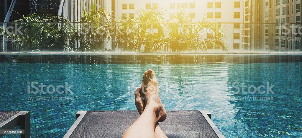 Relaxing in holidays, Asian guy feet on sun bathing bed stock photo